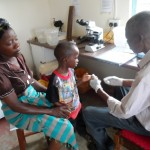 LAB mnager takes malaria sample from child